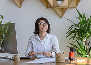 Happy desk worker with indoor plants on her desk